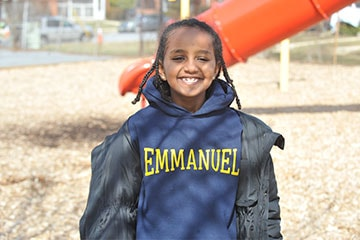 Student Smiling at Camera on Playground