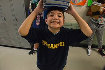 Student Smiling at Camera with Books on His Head